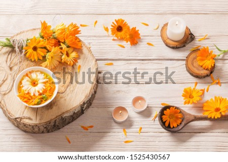 Medicinal flowers of calendula with burning candles  on white wooden background #1525430567