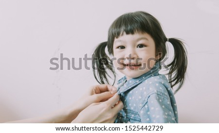 Mother buttoned the shirt for the child. #1525442729