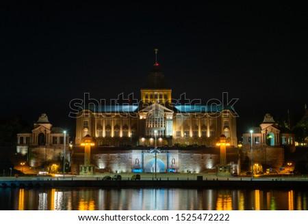 Szczecin. Night view from across the river to the illuminated historic center. Odra river. Chrobry embankments in Szczecin Royalty-Free Stock Photo #1525472222