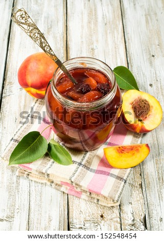 peach jam in a glass jar with fresh peaches #152548454