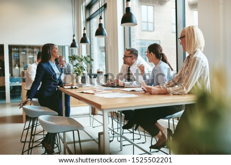 Smiling group of diverse businesspeople discussing paperwork together during a meeting around a table in a modern office #1525502201