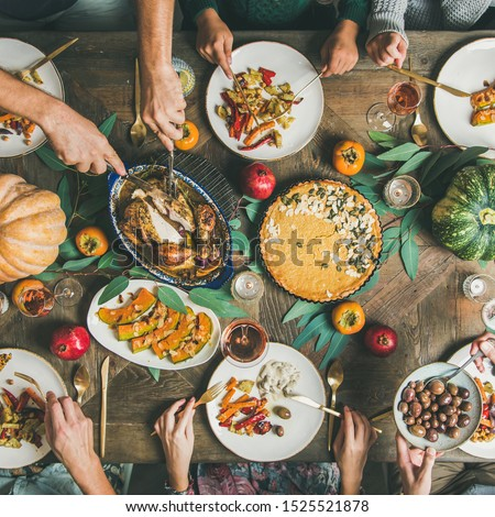 Thanksgiving or Friendsgiving holiday celebration party. Flat-lay of friends feasting at Thanksgiving Day table with turkey, pumpkin pie, roasted vegetables, fruit and rose wine, top view, square crop #1525521878