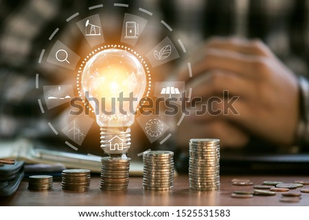 Business man holding light bulb on the Green background nature and writing on note book it for financial #1525531583