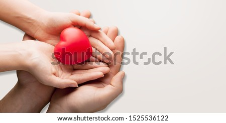 An adult, mother and child hold a red heart in their hands. Concept for charity, health insurance, love, international cardiology day. #1525536122