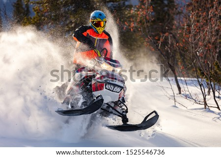 the guy is flying and jumping on a snowmobile on a background of winter forest  leaving a trail of splashes of white snow. bright snowmobile and suit without brands. extra high quality #1525546736
