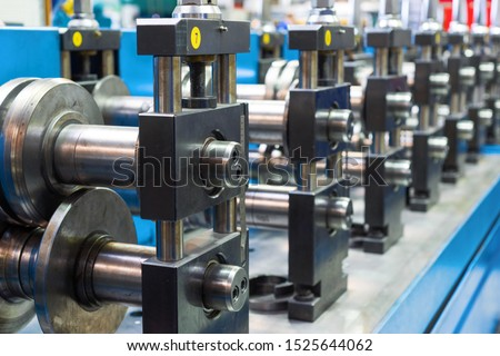 Modern machine for the manufacture of metal profiles. The main working bodies of the machine, metal rolls. Roller mill with many round steel rollers. #1525644062