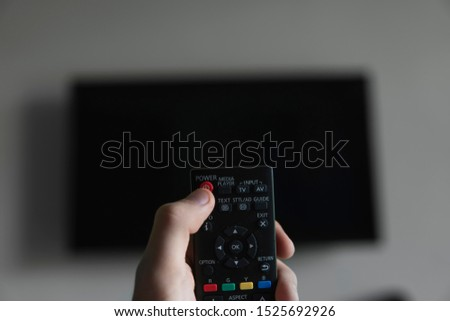 The man with the remote control in hand want switch on the TV and presses the button on the remote control. Remote control in hand closeup. #1525692926