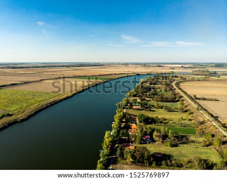 Tisa river in Serbia in Serbia,Vojvodina meandering between agriculture fields. Aerial view above Tisa river in Serbia. Rural countryside landscape in Vojvodina #1525769897