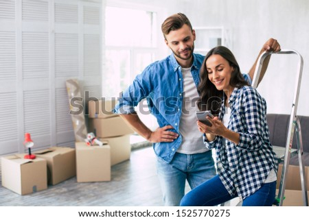 Checking for ideas. Handsome man in denim outfit is checking something in the smartphone together with his gorgeous wife, leaning on the ladder with his left hand. House moving concept. #1525770275