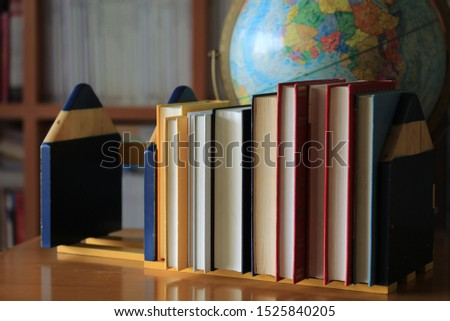 Close-up of several books arranged on a bookshelf in the library. Bookshelf and globe in the background selective focus and shallow depth of field #1525840205