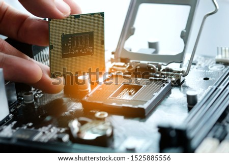 Hand of computer engineering brings computer cpu processor memory change components into socket processor for maintenance.Technology and development concept #1525885556