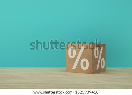 Percentage sign symbol icon with paper cube block on wooden table and blue background. #1525939418