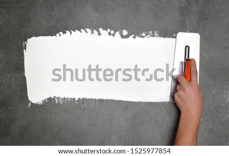 Hand with a spatula, the process of applying a layer of putty. Renovation of apartments. Repair the walls. Free space for advertising, text. #1525977854
