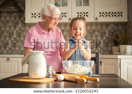 Cute little girl and her grandmother cooking on kitchen. #1526016245