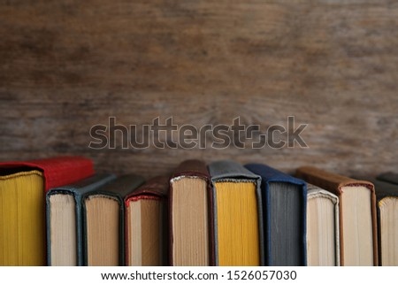 Stack of hardcover books on wooden background. Space for text #1526057030