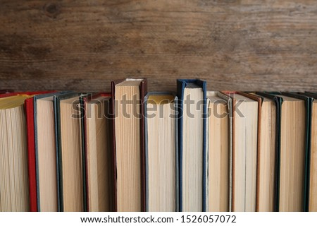 Stack of hardcover books on wooden background #1526057072