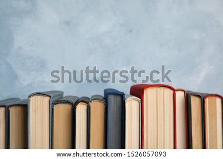 Stack of hardcover books on light blue background. Space for text #1526057093