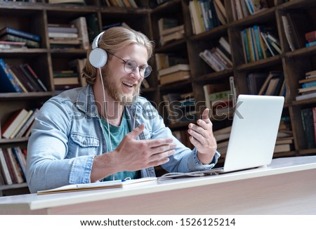 Happy male student online teacher wear headphone talk video calling looking at laptop computer screen do conference chat communicate with skype tutor, distance education e learning course in library #1526125214