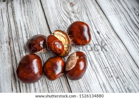 Chestnuts on a wooden background. Chestnuts top view. Chestnut autumn background. Chestnuts in autumn on wooden background #1526134880