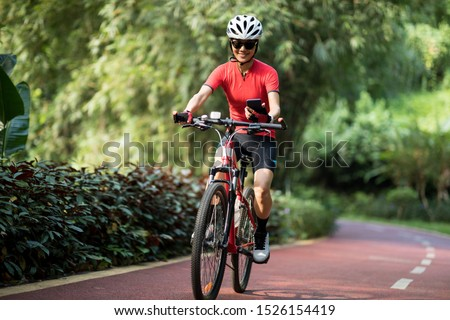 Riding on bike path,using smartphone while riding bike on sunny day