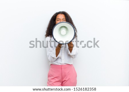 young pretty black woman with a megaphone against white wall Royalty-Free Stock Photo #1526182358