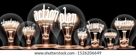 Photo of light bulb group with shining fibers in a shape of Action Plan, Strategy, Goal and Target concept related words isolated on black background #1526206649