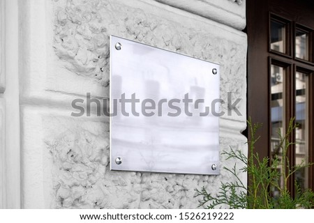 Blank silver glass signboard on textured wall mockup. Empty wal mounted signplate mock up. Clear outdoor plexiglass signage for hotel or store info mokcup template.