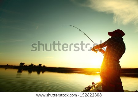 Young man fishing on a lake from the boat at sunset Royalty-Free Stock Photo #152622308