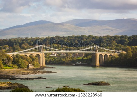 The Menai suspension bridge designed by Thomas Telford and completed in 1826 to connect the mainland with the island of Anglesey Wales Royalty-Free Stock Photo #1526228960