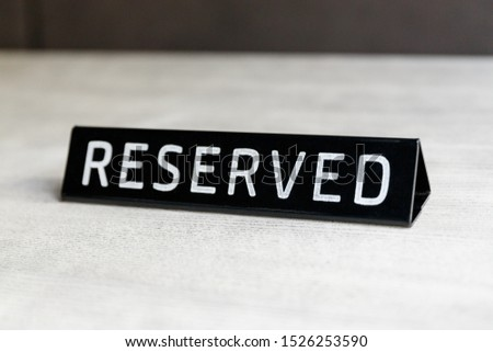 Black glossy reserved sign on a table in cafe or restaurant