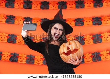 Image of happy witch girl in black halloween costume taking selfie photo with carved pumpkin isolated over orange wall