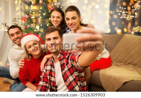 celebration and holidays concept - happy friends with glasses celebrating christmas at home party and taking selfie by smartphone #1526309903