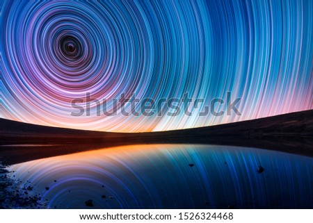 Beautiful night landscape, old volcano, crater lake. The colorful star trails on the sky. Night timelapse photography.