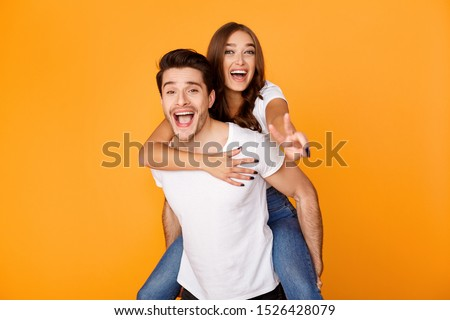 Young man giving piggyback ride to woman, showing peace sign over yellow background #1526428079