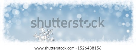 Large banner picture with beautiful ice crystal lying in the snow and glittering in the sun, bokeh in the blue background