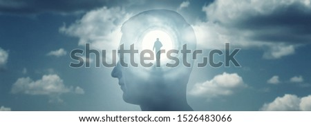 A silhouete of a man with rays of light emanating from the brain as a symbol of the power of thinking. Concept on the topic of psychiatry (bipolar disorder, schizophrenia), psychology, religion. #1526483066