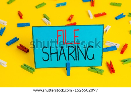 Text sign showing File Sharing. Conceptual photo transmit files from one computer to another over a network Colored clothespin papers empty reminder yellow floor background office. #1526502899