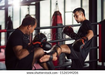 Asian kickboxing player and him trainer in boxing gym, this photo can use for muay thai, sport, thai, combat and coach concept Royalty-Free Stock Photo #1526544206