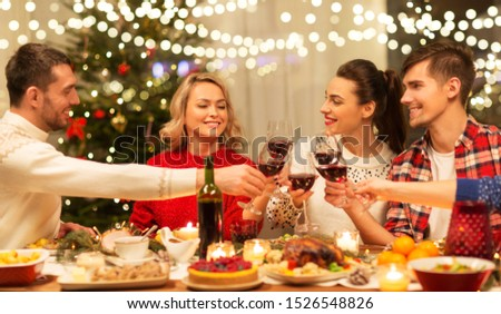 holidays and celebration concept - happy friends having christmas dinner at home, drinking red wine and clinking glasses #1526548826