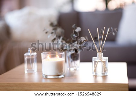 decoration, hygge and aromatherapy concept - aroma reed diffuser, burning candle, branches of eucalyptus populus and perfume on table at home #1526548829