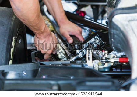 Moscow, Russia - July 22, 2017: Нands of a mechanic adjusting the suspension of a DTM racing car #1526611544