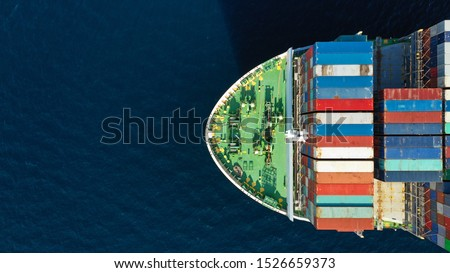 Aerial top down photo of Container cargo ship carrying load in truck-size colourful containers in deep blue open ocean sea