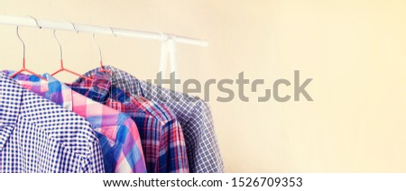 Many long sleeve colorful checkered shirts on hangers in the showroom. Shopping and fashion with a selection in a wide range concept. #1526709353