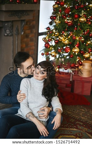 The young happy couple, in warm sweaters. Young handsome man kissing a beautiful girlfriend near the fireplace and Christmas tree in the background. Christmas celebration and New year holidays #1526714492
