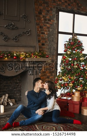 The young happy couple, in warm sweaters and red socks, hugging and sitting on the authentic carpet near the fireplace and Christmas tree. Christmas celebration and New year holidays #1526714498