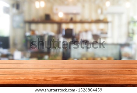 Wood table in blurry background of modern restaurant room or coffee shop with empty copy space on the table for product display mockup. Interior restaurant counter design concept. #1526804459