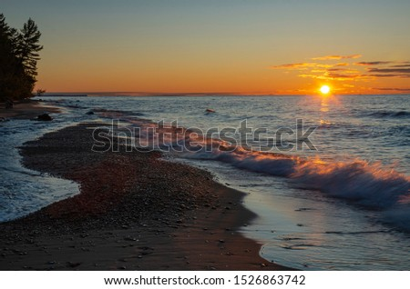 The sun sets into Lake Superior at the mouth of the Hurricane River in Pictured Rocks National Lakeshore in Alger County, Michigan