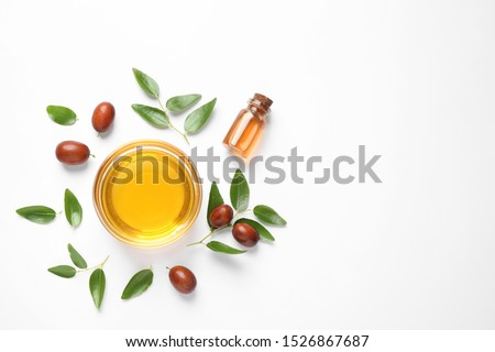 Bowl with jojoba oil and seeds on white background, top view #1526867687