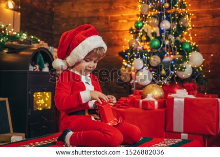 Little boy decorating xmas tree and opening gifts. New Year. Christmas time. Elf child. Winter shopping sale. New Year surprise present. Merry and bright christmas #1526882036
