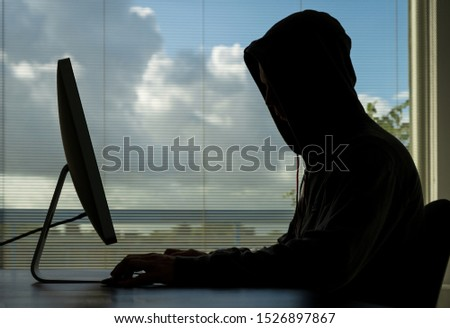 Hacker doing his crime on a desktop computer in broad daylight. Royalty-Free Stock Photo #1526897867